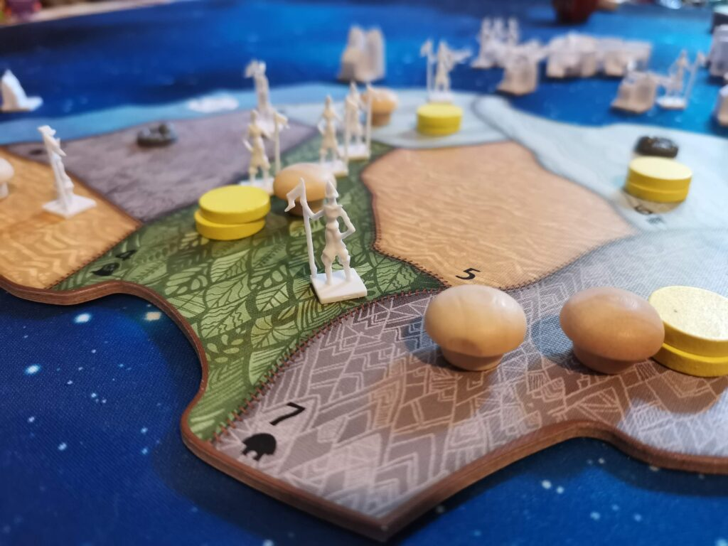 plastic and wooden playing pieces on the map board of spirit island